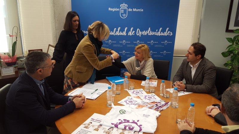 La secretaria de Igualdad y Responsabilidad Social, María Aránzazu Bilbao de Cala, poniéndole la pulsera 'Nos preocupa tu vida' a la consejera de Familia e Igualdad de Oportunidades, Violante Tomás