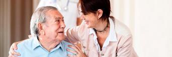 Asistenta Social con un señor de tercera edad en una Residencia realizando un gesto cariñoso